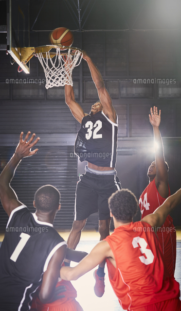 young male basketball player dunking the ball into hoop with