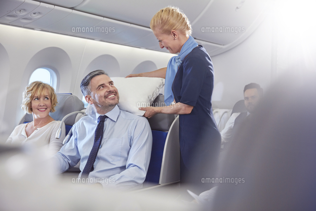 smiling flight attendant adjusting pillow for businessman in first
