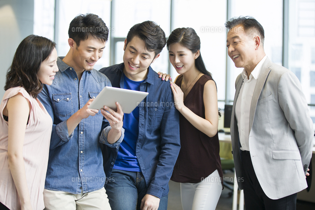 businessman showing digital tablet to colleagues 11091022789 写真