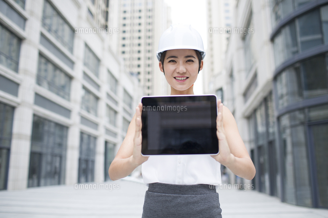 female architect showing a digital tablet outdoors 11091024077