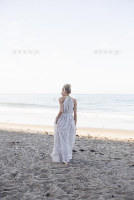 blond woman wearing a long dress standing on a sandy beach