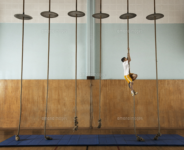 a child climbing up a rope in a school gym 11093008914 写真素材