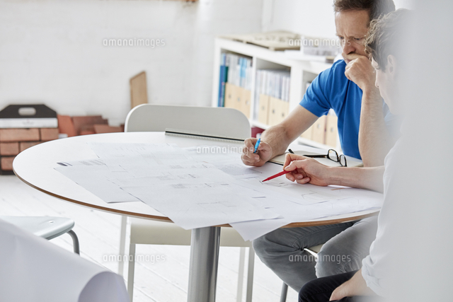 a modern office two people at a meeting discussing paper plans and