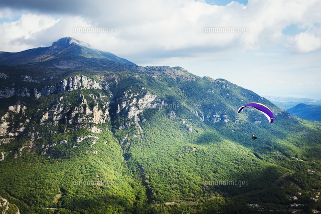 a paraglider in flight over a valley in the mountains 11093013468