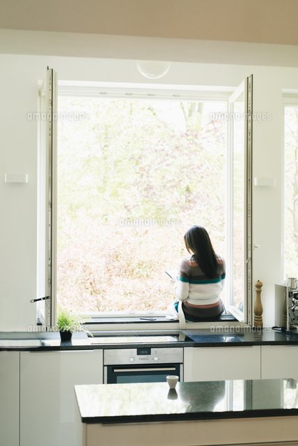 woman in kitchen sitting on windowsill 11094014722 写真素材
