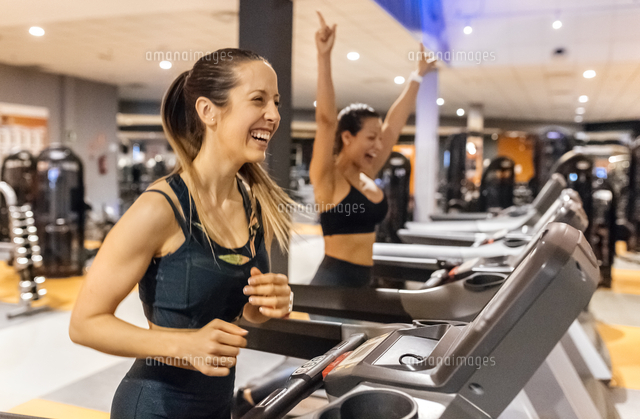 two happy women working out in gym on a treadmil 11094023195 写真