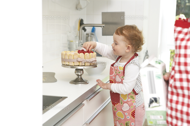 mother and little daughter baking cake together in their kit