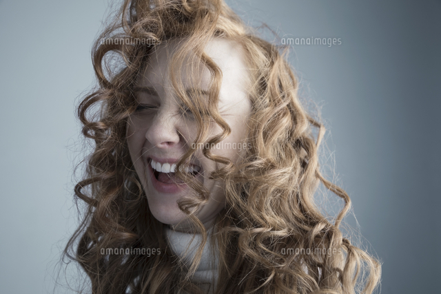 portrait playful caucasian woman with messy red curly hair in face