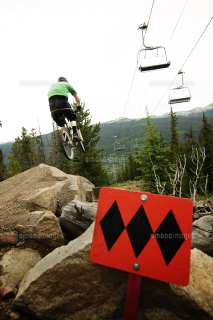 mountain biker riding down on rocks in forest 11100010563 写真