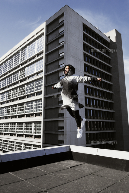 young man jumping on roof of building 11100032460 写真素材