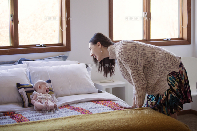 Side view of happy woman looking at cheerful baby girl lying on bed at home