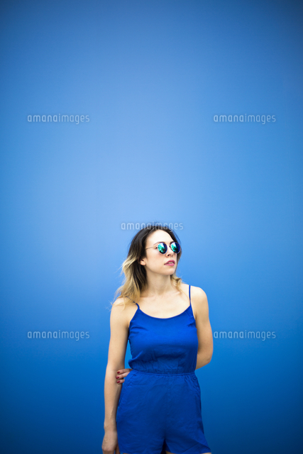young woman standing against blue wall 11100040584 写真素材