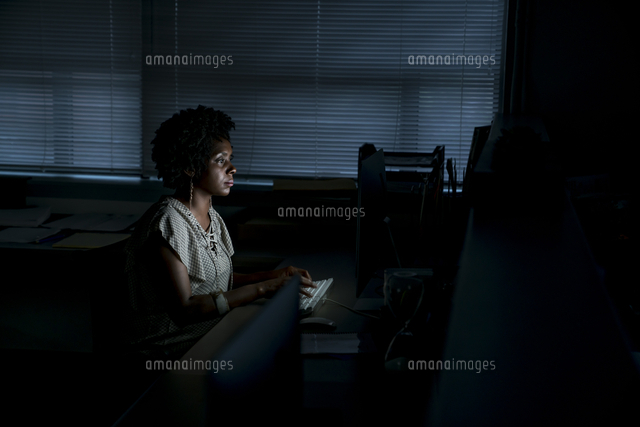 side view of businesswoman working on desktop computer while sitting