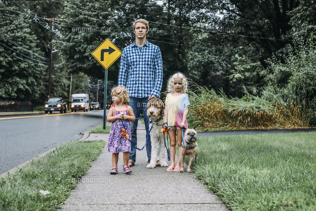 father and daughters standing on footpath with dogs at lawn