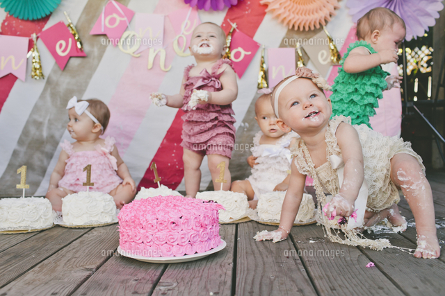 cute baby girls with birthday cakes on floorboard at party