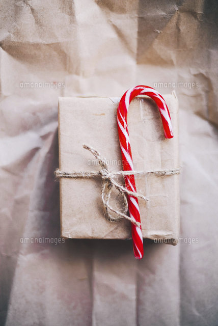 candy cane tied up with christmas present on brown paper 11100079422