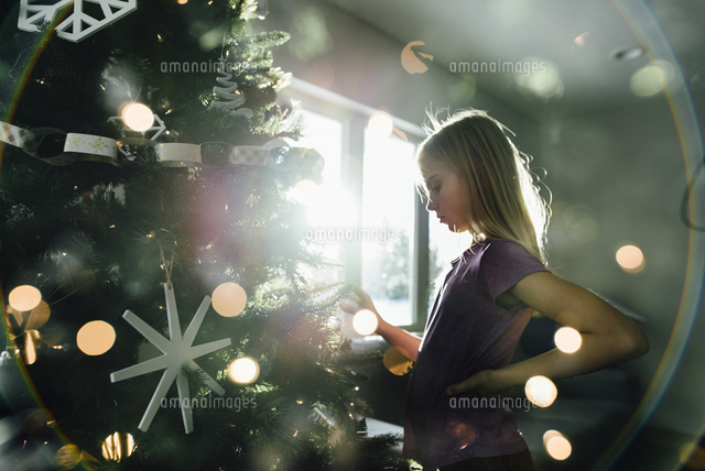 Side view of girl standing by illuminated Christmas tree at home