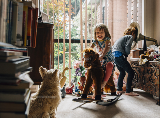 Happy siblings playing at home with dog sitting in foreground