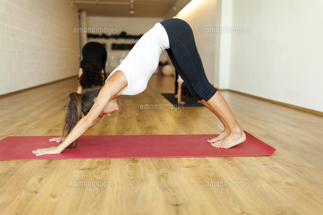 female instructor with mother and son practicing downward facing dog