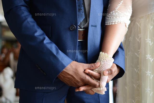 作品番号:11115001336 作品タイトル:Midsection Of Newly Wed Couple Holding Hands During Wedding