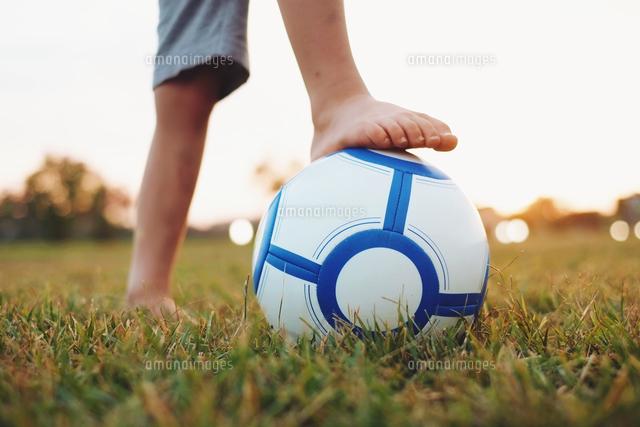 作品番号:11115003912 作品タイトル:Low Section Of A Boy Holding Ball Under Foot