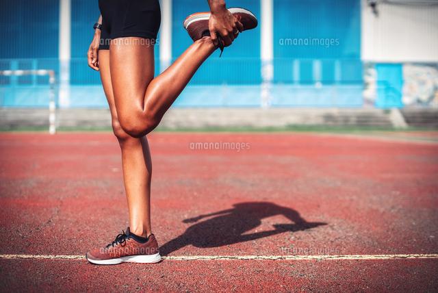 作品番号:11115006312 作品タイトル:Low Section Of Female Athlete Stretching Leg On Sports Track