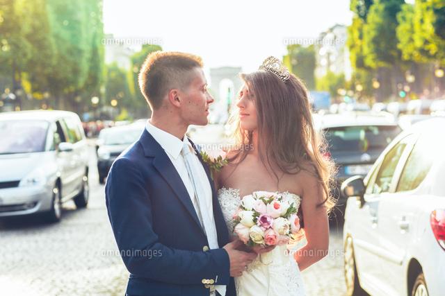 作品番号:11115008368 作品タイトル:Young Wedding Couple Standing With Flower Bouquet On Street In City