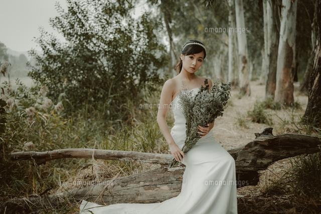 作品番号:11115008593 作品タイトル:Portrait Of Woman Holding Bouquet While Sitting On Log In Forest