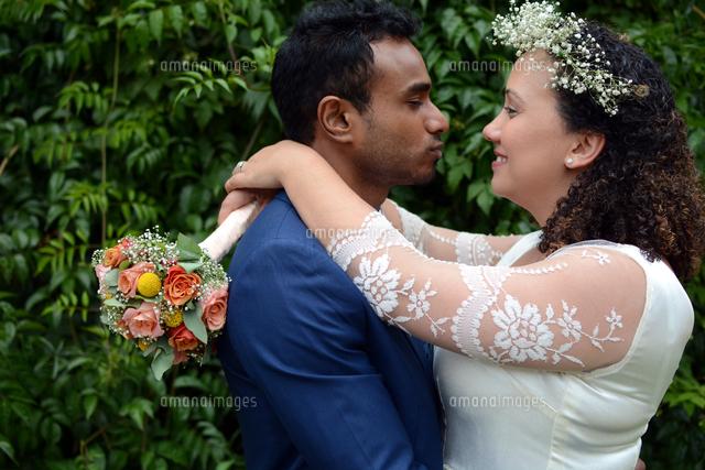 作品番号:11115012776 作品タイトル:Close-up Of Bride And Groom Embracing While Standing Against Plants At Park