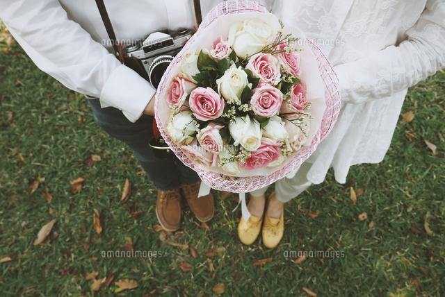 作品番号:11115018526 作品タイトル:Low Section Of Bride And Groom Holding Bouquet While Standing On Grassy Field
