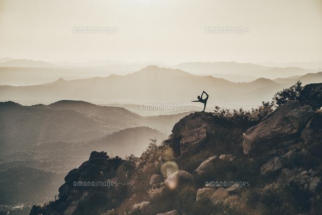 作品番号:11115021525 作品タイトル:Mid Distance View Of Silhouette Woman Exercising On Rock Against Mountains During Sunset