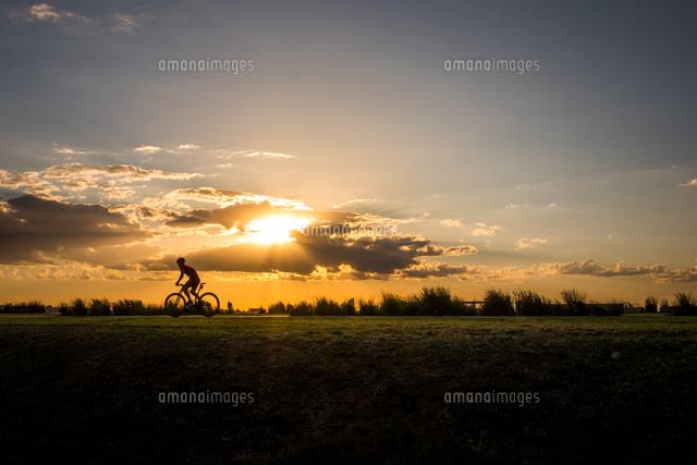 作品番号:11115021545 作品タイトル:Man Cycling Of Field Against Sky During Sunset