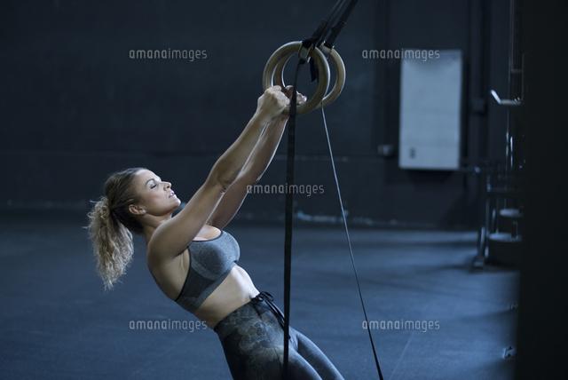 作品番号:11115022009 作品タイトル:Young Woman Exercising On Gymnastic Rings At Gym
