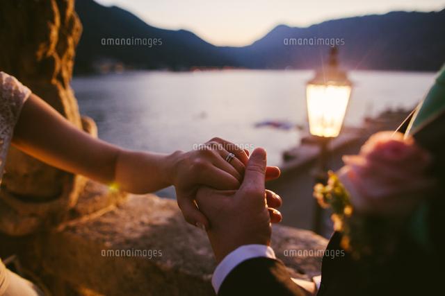 作品番号:11115025176 作品タイトル:Close-up Of Couple With Holding Hands At Lake