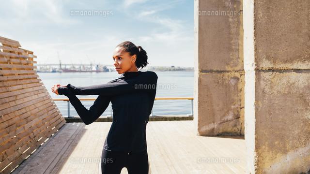 作品番号:11115026506 作品タイトル:Young Woman Stretching On Footpath Against Sky