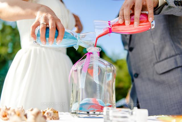 作品番号:11115034907 作品タイトル:Midsection Of Bride And Groom Pouring Sand In Container At Wedding