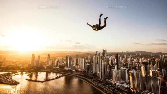 作品番号:11115047331 作品タイトル:Man Paragliding In Mid-air In City At Sunset