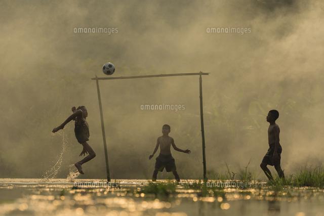 作品番号:11115054139 作品タイトル:Shirtless Boys Playing Soccer On Wet Field During Monsoon