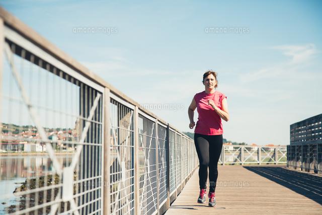作品番号:11115062237 作品タイトル:Woman Jogging On Footbridge In City