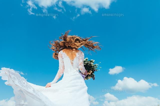 作品番号:11115062990 作品タイトル:Low Angle View Of Woman With Bouquet Standing Against Sky