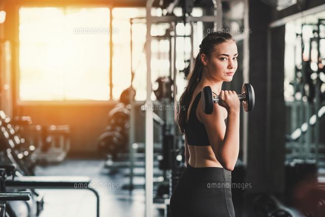 作品番号:11115065060 作品タイトル:Portrait Of Young Woman Lifting Dumbbell In Gym