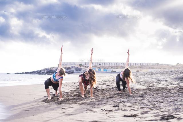作品番号:11115065718 作品タイトル:Young Friends Exercising At Sandy Beach Against Cloudy Sky