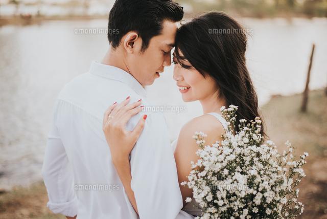 作品番号:11115067196 作品タイトル:Young Couple With White Flowers Romancing Outdoors