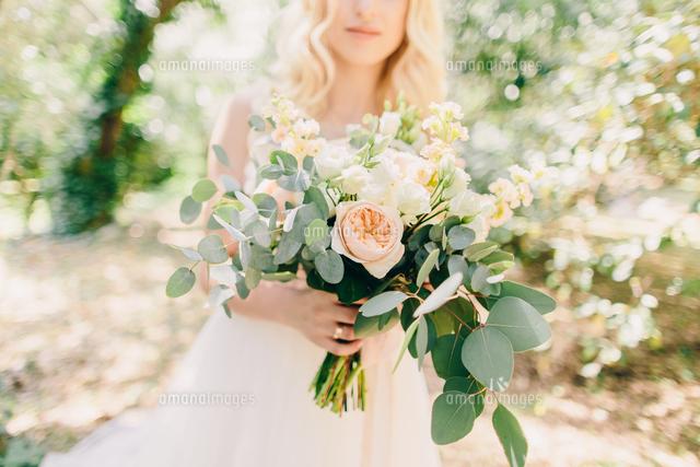 作品番号:11115067295 作品タイトル:Midsection Of Bride Holding Flower Bouquet While Standing At Park