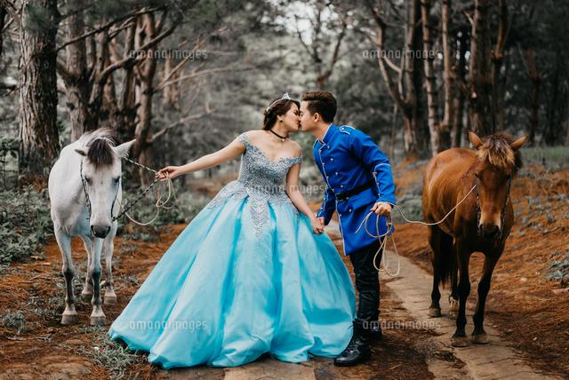 作品番号:11115068128 作品タイトル:Wedding Couple Holding Horses While Kissing On Mouth In Forest