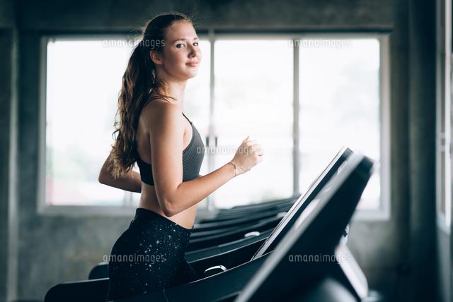 作品番号:11115068373 作品タイトル:Portrait Of Smiling Young Woman Running On Treadmill