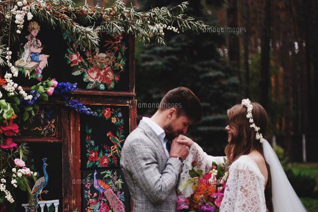 作品番号:11115068549 作品タイトル:Bridegroom Kissing Bride Hand By Plants