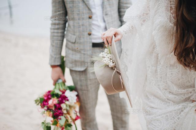 作品番号:11115075241 作品タイトル:midsection of bride with bridegroom holding hat