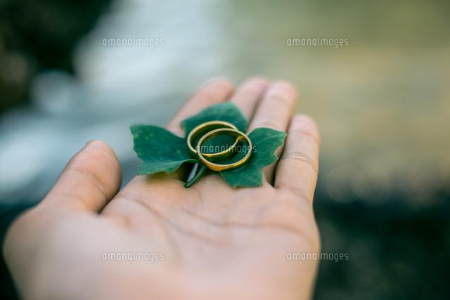 作品番号:11115075632 作品タイトル:close-up of cropped woman hand holding wedding rings with leaf