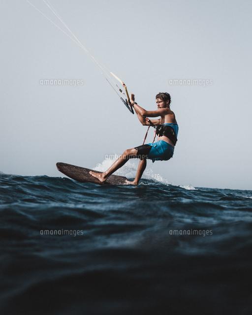 作品番号:11115075782 作品タイトル:side view of man kiteboarding in sea against clear sky